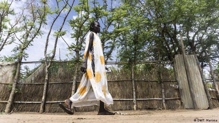 Akwata Umot Okok walks past a fence