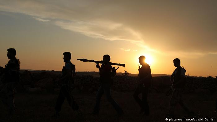 Syrian rebels walk to reposition (picture-alliance/dpa/M. Dairieh)