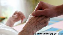 Carer holding hand of aged patient (picture-alliance/dpa/O. Berg)