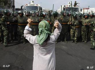 Eine Uiguren-Frau protestiert vor Polizisten (Foto: AP)