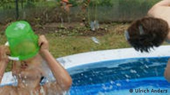 Two young boys play in a pool in the back garden
