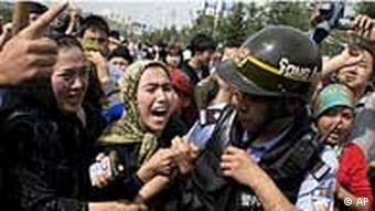 Uiguren-Frauen bedrängen einen Polizisten (Foto: AP)