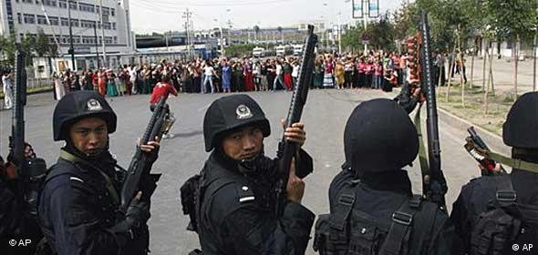 Schwer bewaffnete Polizisten stehen einer Menschenmenge gegenüber ( Foto. AP)