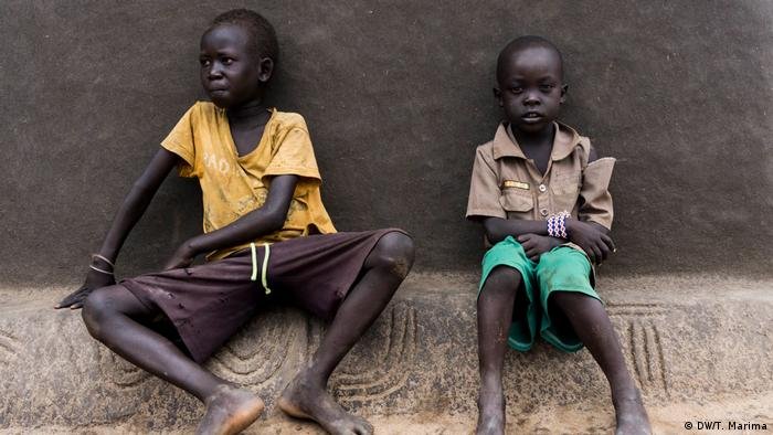Anuak boys in Gorom Refugee Camp, South Sudan sit outside a home decorated with traditional markings (photo: DW/T. Marima)