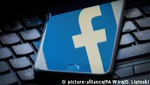 Facebook Logo spiegelt sich in Smartphone
