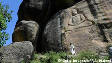 This photo taken on April 26, 2018 shows a Pakistani visitor walking past a seventh-century rock sculpture of a seated Buddha carved into a mountain in Jahanabad town in the northwestern Swat Valley of Pakistan, following a restoration process conducted by Italian archaeologists after the Taliban defaced it in 2007. - The Buddha of Swat, carved on a cliff in the seventh century, was dynamited by the Pakistani Taliban in 2007. Now it has been restored, a powerful symbol of tolerance in the traumatised Pakistani valley. (Photo by ABDUL MAJEED / AFP) / TO GO WITH Pakistan-archaeology-Buddha-Swat,FEATURE by Amelie Herenstein (Photo credit should read ABDUL MAJEED/AFP/Getty Images)