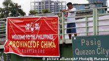 A man tries to remove a tarpaulin banner with the words Welcome to the Philippines, Province of China that was hung from an overpass