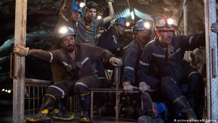 Film still The 33, miners with hard hats and lights in the dark (picture-alliance/B.Aguirre)