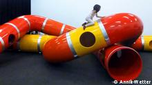 Child climbing on plastic tubes in exhibition (Annik Wetter)