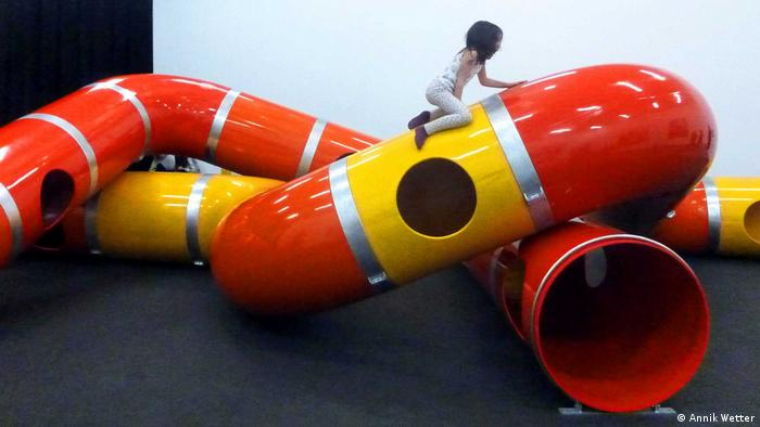 Girl climbs tubes at Playground Project exhibition (Annik Wetter)