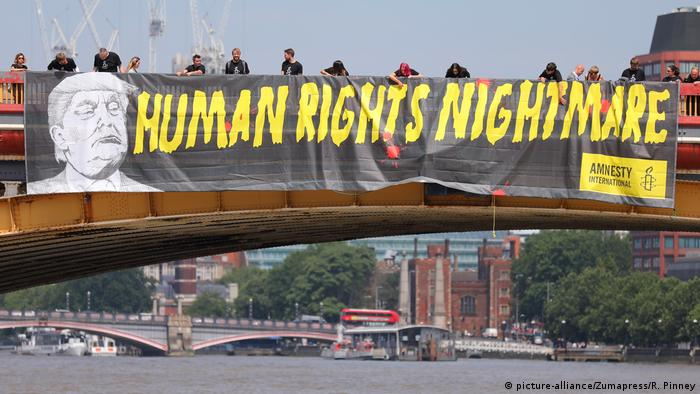 A banner over Vauxhall Bridge in London bearing an image of Donald Trump and the words 'Human Rights Nightmare' in bright yellow letters