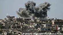 FILE - This Thursday, July 5, 2018 file photo provided by Nabaa Media, a Syrian opposition media outlet, shows smoke rising over buildings that were hit by Syrian government forces bombardment, in Daraa province, southern Syria. Syrian activists and state media said Thursday, July 12, 2018 that the rebels have agreed to surrender Daraa, the first city to revolt against President Bashar Assad with Arab Spring-inspired protests seven years ago, to government forces. (Nabaa Media via AP, File) |
