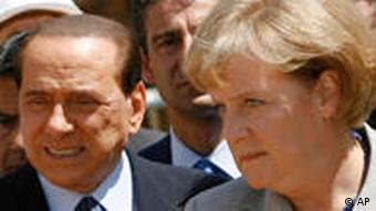 Italian Prime Minister Silvio Berlusconi, center, is flanked by German Chancellor Angela Merkel during a visit to the village of Onna, central Italy, three months after a devastating earthquake, on the sidelines of a G8 meeting Wednesday, July 8, 2009. The leaders of the Group of Eight nations, united in their desire to work together to fight the worst economic crisis since the Depression, divided on how much longer they need to keep the stimulus going, are discussing Wednesday how to coordinate their exit strategies once their economies are stable. (AP Photo/Markus Schreiber, Pool)
