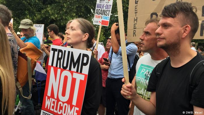Protesters hold signs as Donald Trump arrives in London (DW/B. Wesel)