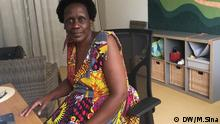 Esther Mujawayo-Keiner sitting at her office desk at the Psychosocial Center for Refugees in Düssseldorf. She is looking into the camera. In the background are chairs and a colorful painting. (DW/M.Sina)