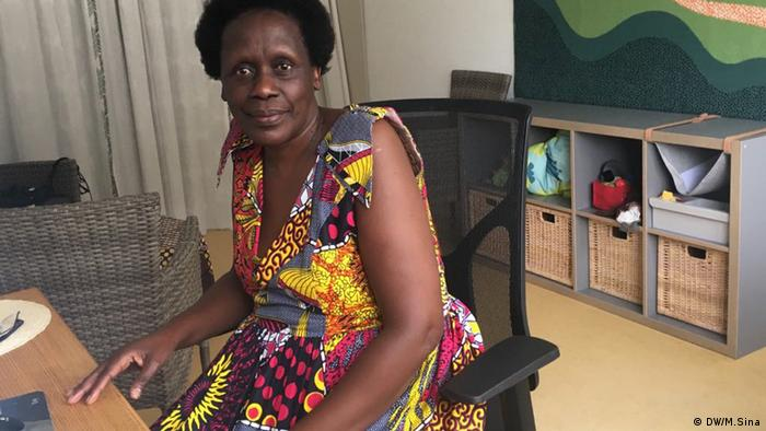 Esther Mujawayo-Keiner sitting at her office desk at the Psychosocial Center for Refugees in Düssseldorf. She is looking into the camera. In the background are chairs and a colorful painting.