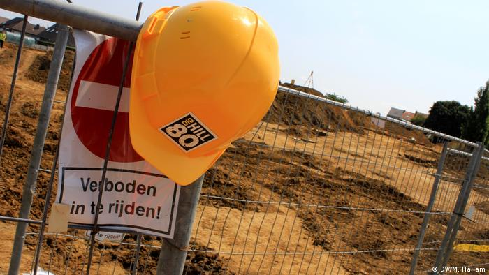 Archaeological dig site at Wijtschate, Belgium, excavating remnants of a World War I trench network; photo taken 06.07.2018. A protective hard hat with the project's Dig Hill 80 logo hangs on the security fence cordoning off the site. (DW/M. Hallam)