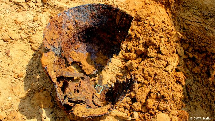 Archaeological dig site at Wijtschate, Belgium, excavating remnants of a World War I trench network; photo taken 06.07.2018. A soldier's helmet, with parts of the leather strap still intact, moments after it was unearthed. (DW/M. Hallam)