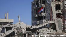 The Syrian national flag rises in the midst of damaged buildings in Daraa-al-Balad, an opposition-held part of the southern city of Daraa, on July 12, 2018. - Syria's army entered rebel-held parts of Daraa city , state media said, raising the national flag in the cradle of the uprising that sparked the country's seven-year war, followig a deal for rebels to hand over their heavy weapons in Daraa al-Balad and other opposition-held parts of the city. (Photo by Mohamad ABAZEED / AFP) (Photo credit should read MOHAMAD ABAZEED/AFP/Getty Images)