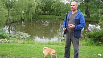 Человек с фотоаппартаом на фоне пруда