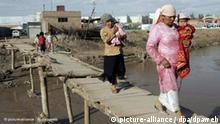 Islamic women of the Uyghur ethnic group carry their children over a bridge in Kashgar, in China's Xinjiang Uyghur Autonomous Region, 29 August 2005. The approximate 3.5 million Uyghur women in Xinjiang continue to lack the education and independence of their male counterparts, said a regional expert on Tuesday, 20 September 2005. Traditional values dictating the domestication of females have also prevented economic development sought after by Beijing, the expert said. Foto: Michael Reynolds +++(c) dpa - Report+++