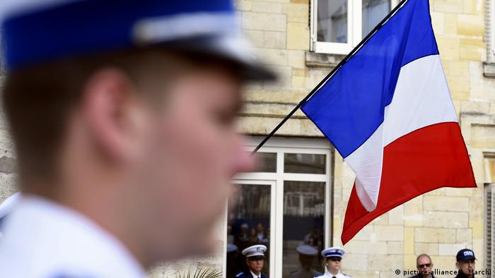 French policeman in front of a French flag (picture-alliance/A. Marchi)
