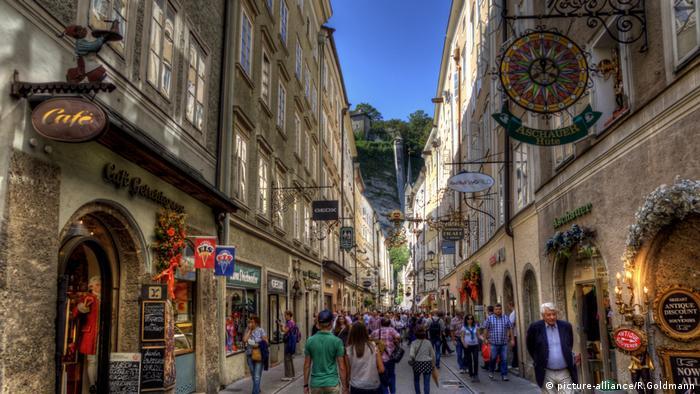 Tourists walk down the narrow Getreidegasse.