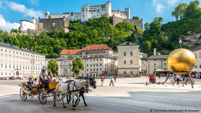 A view of Chapter Square, with a horse-drawn carriage and view of the fortress above.