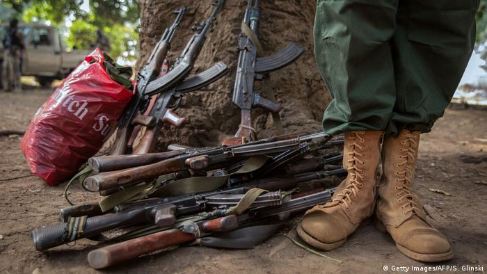 The feet of a former child soldier standing next to rifles