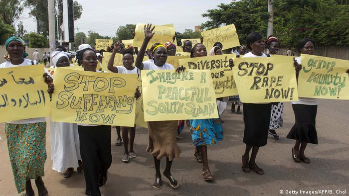 Women in South Sudan demonstrating for rights and peace hold up signs saying Stop rape now and Imagine a peaceful South Sudan