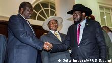 July 7, 2018. President of South Sudan, Salva Kiir (R) shakes hands with arch-rival South Sudan's opposition leader Riek Machar (L) during peace talks at Uganda's statehouse in Entebbe where they were received by Ugandan President Yoweri Museveni (C) on July 7, 2018. (Photo by SUMY SADURNI / AFP) (Photo credit should read SUMY SADURNI/AFP/Getty Images)