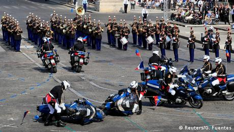 Two gendarmes attempt to right their motorcycles after colliding during the Bastille Day parade (Reuters/G. Fuentes)