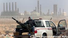 FILE - In this March 5, 2011 file photo, an anti-government rebel sits with an anti-aircraft weapon in front an oil refinery in Ras Lanouf, eastern Libya. The United States France, Germany, Italy, Spain and Britain have called upon forces loyal to a Libyan general to withdraw from three eastern oil terminals seized earlier this week, in a statement Monday, Sept. 13, 2016. The oil-rich North African country slid into chaos after the 2011 uprising that toppled and killed Moammar Gadhafi. (AP Photo/Hussein Malla, File) |