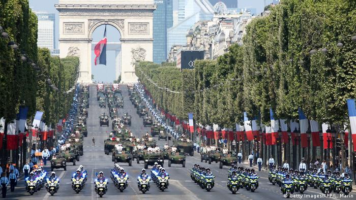 Gendermes on motorcycles followed by armored vehicles and tanks drive down the Champs-Elysees with Arc de Triomphe in the background (Getty Images/AFP/L. Marin)