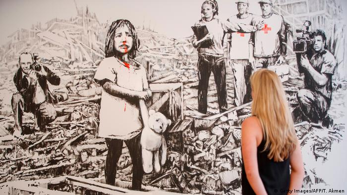 Black-and-white picture by Banksy showing child in ruins of war and media looking on (Getty Images/AFP/T. Akmen)