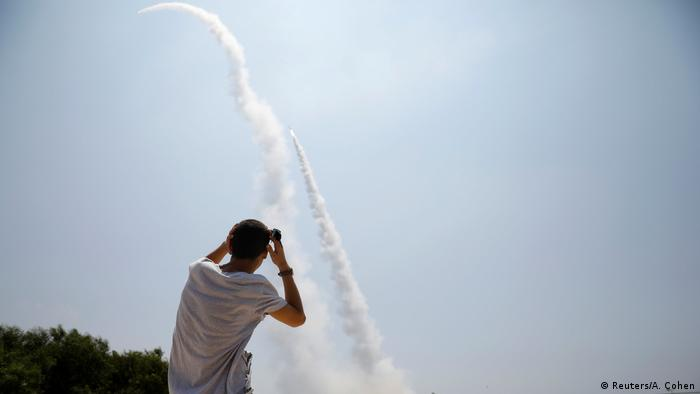 A man looks on as a rocket shoots up into the sky (Reuters/A. Cohen)