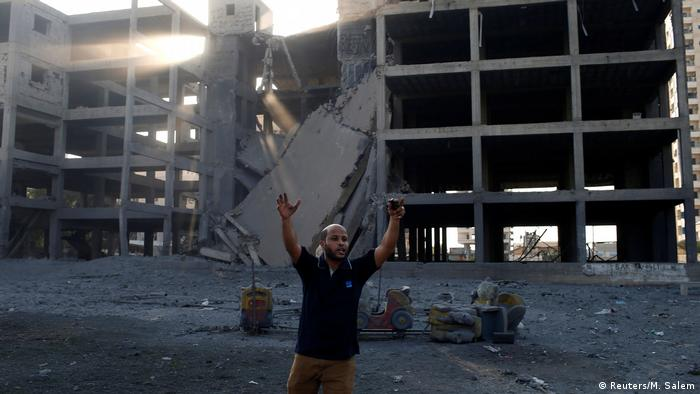 A Palestinian man throws up his arms up after an Israeli airstrike on a building in Gaza City (Reuters/M. Salem)