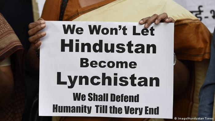 A protester holds a placard during a demonstration against the mob lynchings in the India