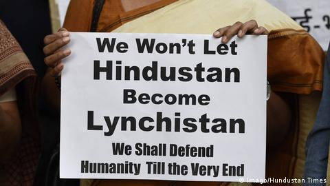 A protester holds a placard during a demonstration against the mob lynchings in India