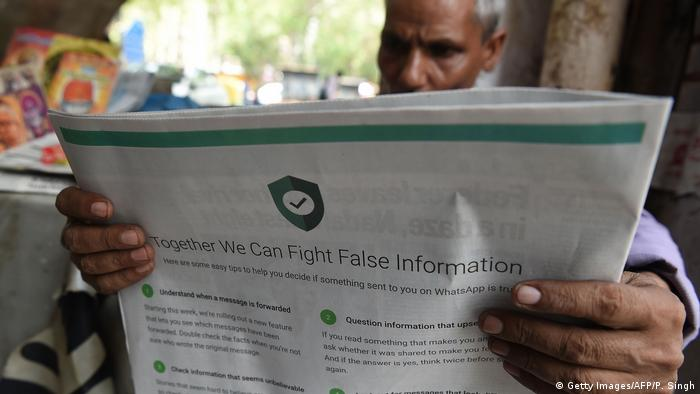 An Indian newspaper vendor reading a newspaper with a full back page advertisement from WhatsApp intended to counter fake information
