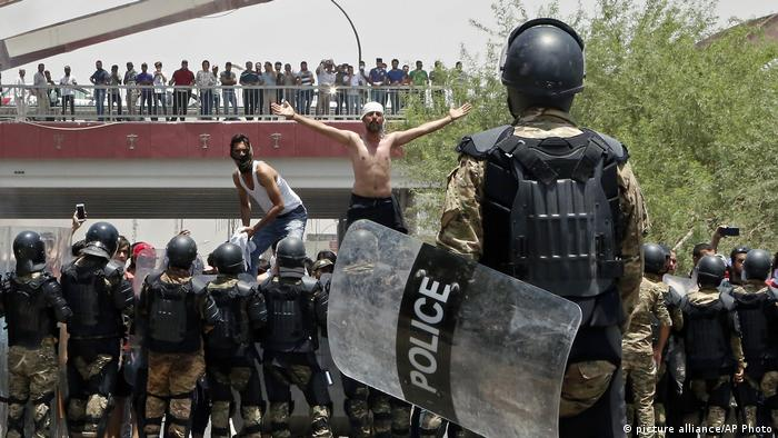 Iraqi riot police prevent protesters from storming the provincial council building during a demonstration in Basra