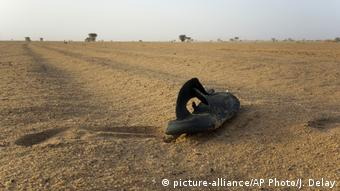Abandoned sandal lies in the sand with the desert stretching in the distance