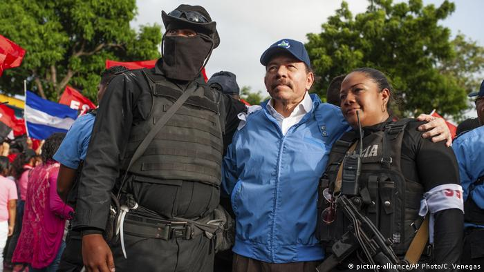 72-year-old Daniel Ortega (center) poses with two anti-riot police officers (picture-alliance/AP Photo/C. Venegas)