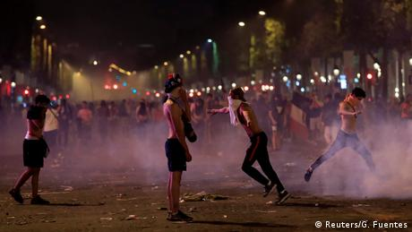 People with shirts to cover their face from smoke bombs in Paris