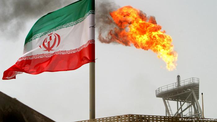 An Iranian flag stands next to an oil production platform (Reuters/R. Homavandi)