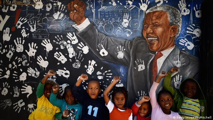 Johannesburg children in front of a mural of Nelson Mandela (Getty Images/J. Mitchell)