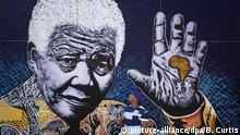 South African artist John Adams works on a giant acrylic-on-canvas painting of Nelson Mandela in the driveway of his house in a suburb of Johannesburg, South Africa, Monday, July 15, 2013. Adams said he felt driven to create the painting as thanks to Mandela for creating educational opportunities that enabled him to become an artist, and plans to auction the painting, the proceeds of which will fund children's charities. (AP Photo/Ben Curtis) |