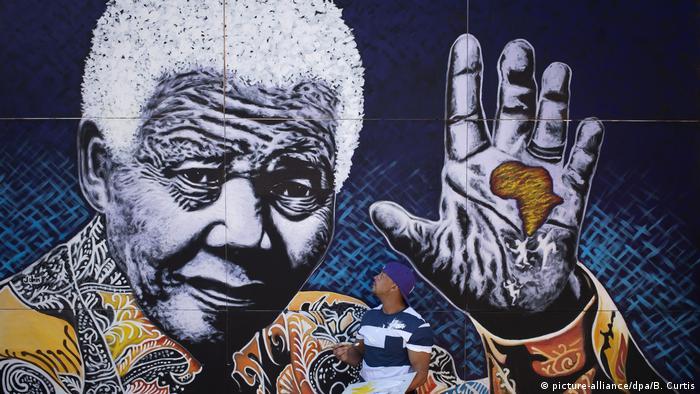 South African artist John Adams painting a mural depicting Nelson Mandela