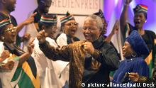 Südafrikas Staatspräsident Nelson Mandela (M) tanzt am Donnerstag im Kongreßzentrum von Baden-Baden mit seiner extra eingeflogenen Lieblingsgruppe Imilonij Ka Ntu vor der Verleihung des Deutschen Medienpreises, rechts die südafrikanische Botschafterin Lindaw Mabuza. Der 80 Jahre alte Friedensnobelpreisträger erhielt die Auszeichnung des Baden-Badener Marktforschungsinstitut Media Control für sein andauerndes Bemühen gegen die Unterdrückung und für die Gleichstellung von Menschen unterschiedlicher Hautfarben. dpa (Digitale Fotografie)  
