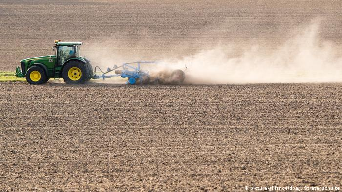 A farmer drives across a field dried out by the heat